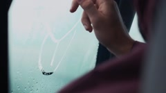 Man drawing on window in car by one finger. Rainy weather outside. Drops Stock Footage