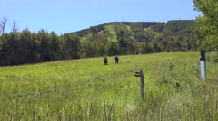 2016: two people walking in a grass field surrounded by trees and hills Stock Footage