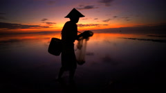 Balinese fisherman in silhouette working on the shoreline of a sunrise beach Stock Footage