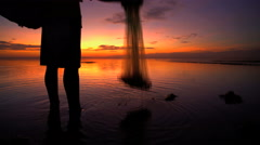 Traditional lifestyle of an Indonesian male fishing on the coastline at sunset Stock Footage
