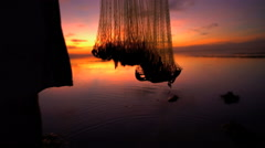 Silhouette of Balinese male fishing in an Indonesian tropical lagoon at sunrise Stock Footage