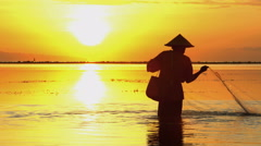 Silhouette of a Balinese man in a conical bamboo hat fishing at sunrise Arkistovideo
