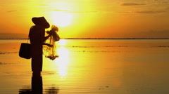 Silhouette of Balinese male at work fishing on Indonesian coastline at dawn Stock Footage
