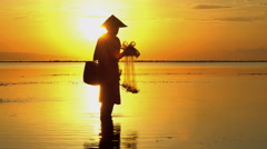 Balinese fisherman in silhouette throwing net into the ocean on a sunrise beach Stock Footage