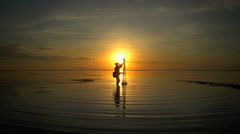 Traditional lifestyle of an Indonesian male fishing on the coastline at sunrise Stock Footage