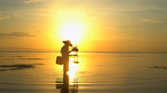Balinese male in silhouette fishing on the Indonesian coastline at sunrise Stock Footage