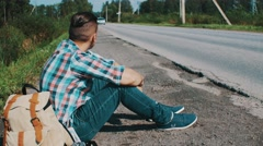 Man sit at road in countryside. Hitchhiking. Waiting. Pick up phone. Backpack Stock Footage