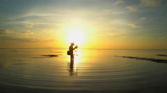 Male fisherman on the shoreline of a tropical lagoon in Bali at sunset Stock Footage