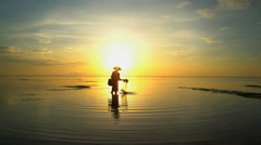 Balinese male in silhouette fishing with a net on a sunset beach in Indonesia Stock Footage