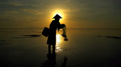 Balinese fisherman in silhouette working on the shoreline of a sunset beach Stock Footage