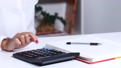 Woman with blueprint counting on calculator and writing to notebook. Close up Stock Footage