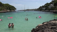 4K Tourist people enjoy take bath in Palma Majorca turquoise water famous bay Stock Footage