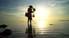 Silhouette of Balinese fisherman throwing a net on the ocean at sunrise Stock Footage