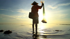 Silhouette of a Balinese man in a conical bamboo hat fishing at sunrise Stock Footage