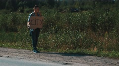 Man stay at road in countryside. Hitchhiking. Smoke cigarette. Sunglasses Stock Footage
