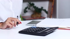 Woman doing calculations in the office and writes resulting numbers. Close up Stock Footage