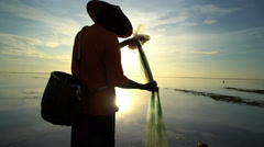 Silhouette of Balinese male fishing in an Indonesian tropical lagoon at sunset Stock Footage
