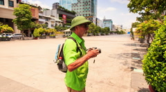 Old Man in Hat Walks Photos on Central Square by Trees Stock Footage
