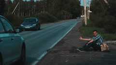 Man with backpack sit at road in countryside. Hitchhiking. Thumb up. Car stops Stock Footage