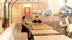 A beautiful girl and a young man talking in a cafe Stock Footage