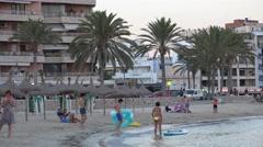 4K Tourist people enjoy sandy beach in Palma Majorca city building traffic road Stock Footage