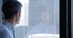 Business man looks through windows and sees reflection in Downtown LA 4K Stock Footage