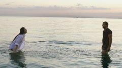 The guy and the girl with water splash in the sea. Spray water on the hand. Stock Footage