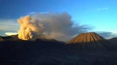 Clouds of smoke and ash from Mount Bromo a barren mud river delta Java Stock Footage