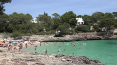 4K Pan right busy beach in exotic Palma Majorca gulf tourist people enjoy summer Stock Footage
