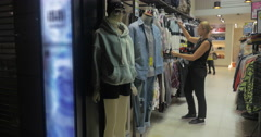 Blond woman smiling while choosing blouses in the shop, Hong Kong, China Stock Footage