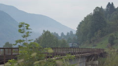 Passenger train passing through the bridge over the mountain river Stock Footage
