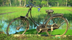 Bicycle by male manual farmer irrigating rice fields with tool Java Indonesia Stock Footage