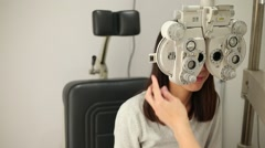 Eyesight measurement to young woman with optical phoropter Stock Footage