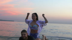 Girl sits on a guy and waving his arms. Man is in water sunset. Stock Footage