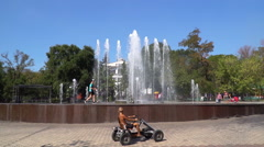 Children ride on the pedal car near the fountain Stock Footage