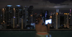 View of woman taking notes in tablet in the swimming pool on the skyscraper roof Stock Footage