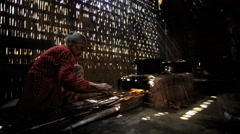 Elderly female traditionally cooking with wood in brick and clay stove Stock Footage