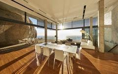 Sun shining in modern luxury home showcase dining room with ocean view Stock Photos
