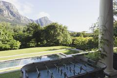 Foosball table on luxury patio overlooking swimming pool and mountain Stock Photos