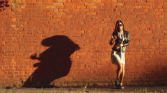 Beautiful young girl dancing near the red brick wall in the sun Stock Footage