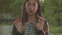 Beautiful young girl looking through the grid  Stock Footage