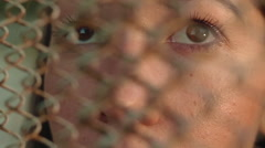 Beautiful young girl looking through the grid eyes close-up Stock Footage