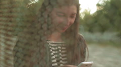 Beautiful young woman read and write messages at the phone on the playground Stock Footage