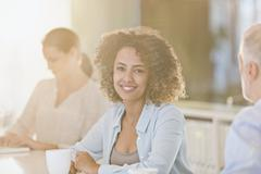 Portrait smiling businesswoman drinking coffee in meeting Stock Photos