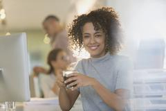 Portrait smiling businesswoman drinking coffee in office Stock Photos