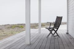 Wooden folding chair on beach house deck Stock Photos