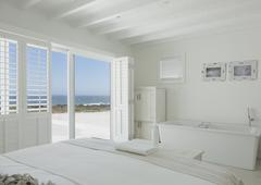 White hotel room with en suite soaking tub and ocean view Stock Photos