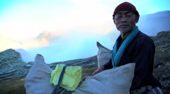 Indonesian male manual worker carrying sulphur blocks from volcano Rim Java Stock Footage