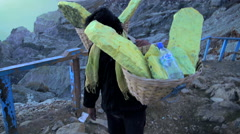 Sulphur mining blocks being carried by manual Indonesian worker Stock Footage