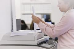 Businesswoman making copies at photocopier in office Stock Photos